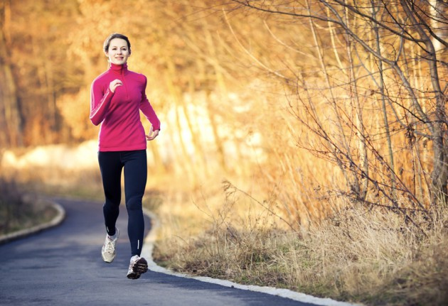 Young woman running outdoors in a city park on a cold fall-winter day (motion blurred image)
